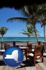 new-york map icon and outdoor furniture on a tropical, oceanfront deck