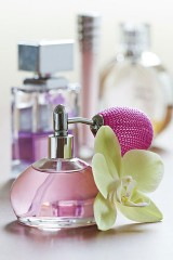 a perfume bottle, with atomizer, and an orchid flower
