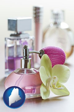 a perfume bottle, with atomizer, and an orchid flower - with Maine icon