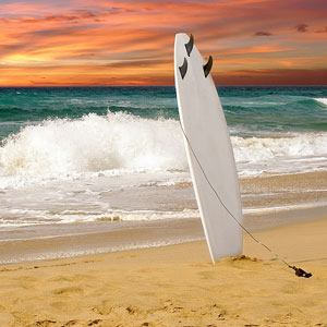 a surfboard standing upright on a sandy beach at sunset
