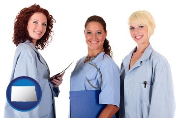 three female doctors wearing hospital uniforms - with North Dakota icon